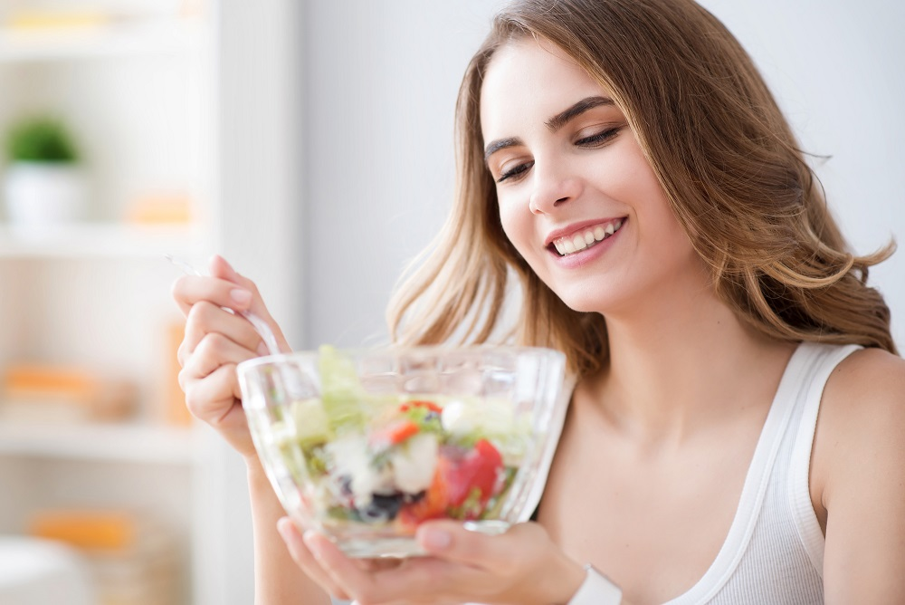 So tasty. Cheerful delighted beautiful woman holding bowl and eating salad while resting at home
