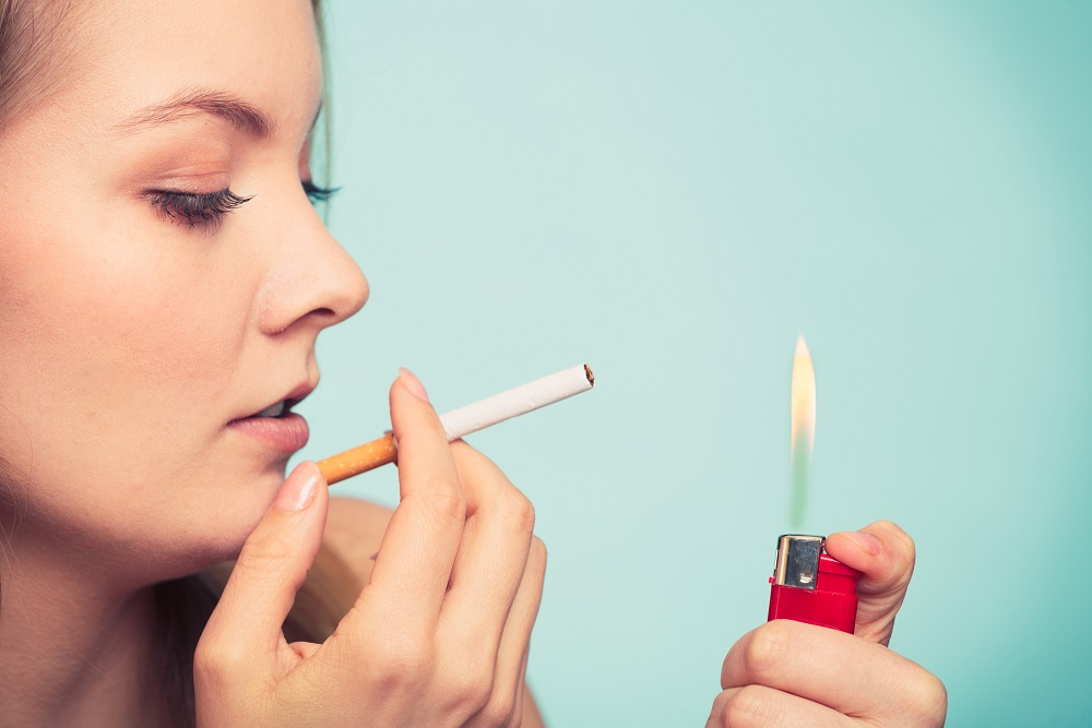 Pretty girl smoking cigarette using lighter. Addicted nicotine problems in young age. Addiction concept.